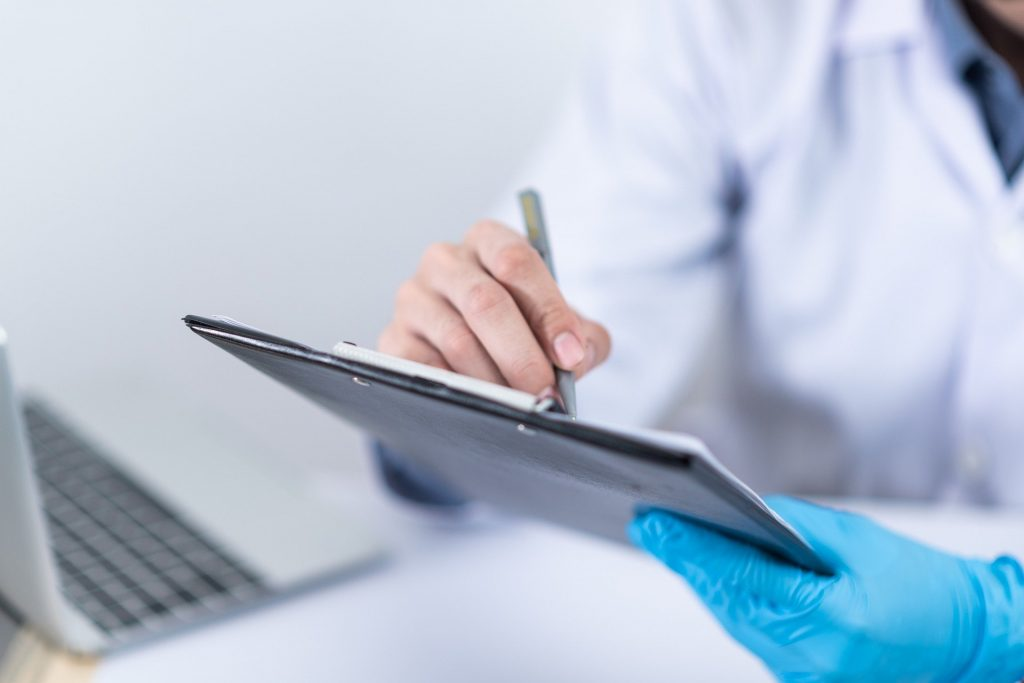 A mobile doctor reviewing a patient's records next to a laptop