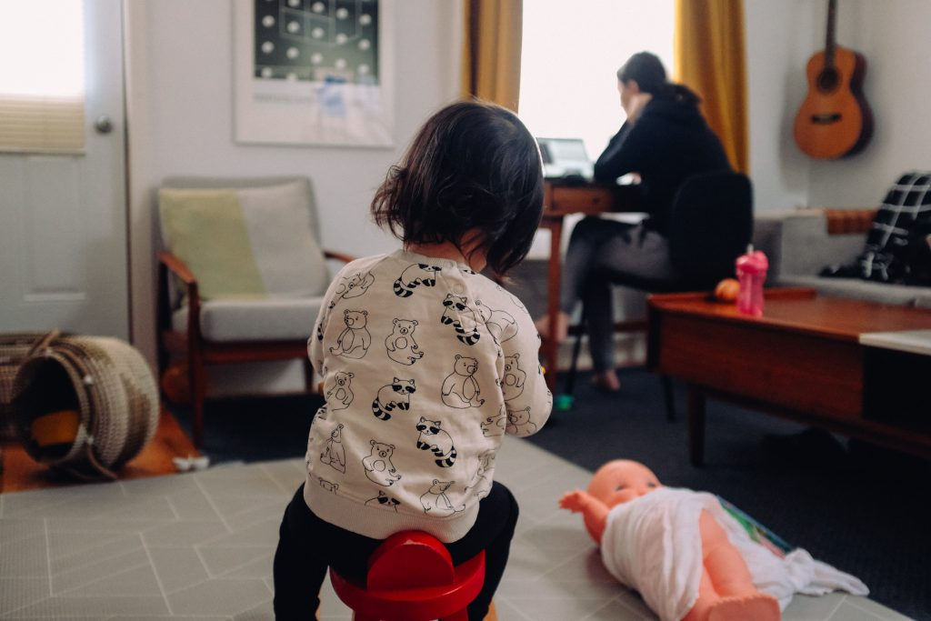 A playing toddler and its mum working from home in the background