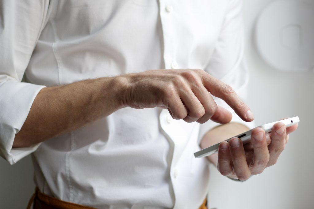A businessman preparing to receive online interpreting services via his smartphone